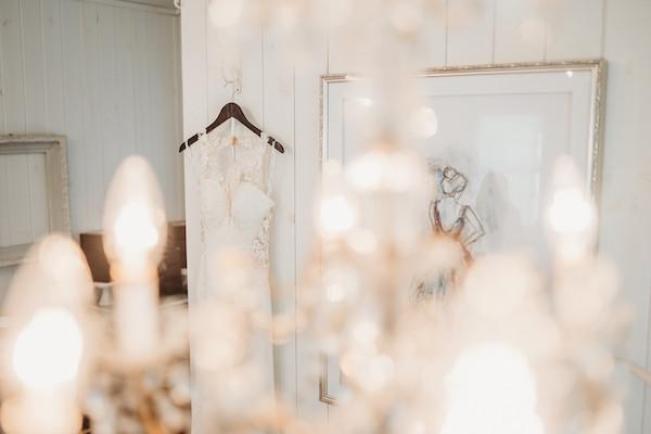 wedding dress hanging on wooden hangar