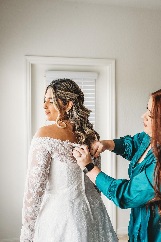 bridesmaid helping the bridge get her wedding dress on