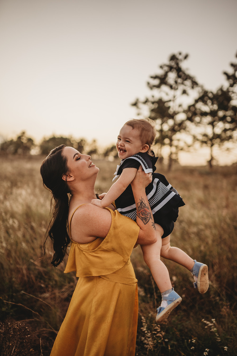 woman holding her baby daughter in a field during sunset