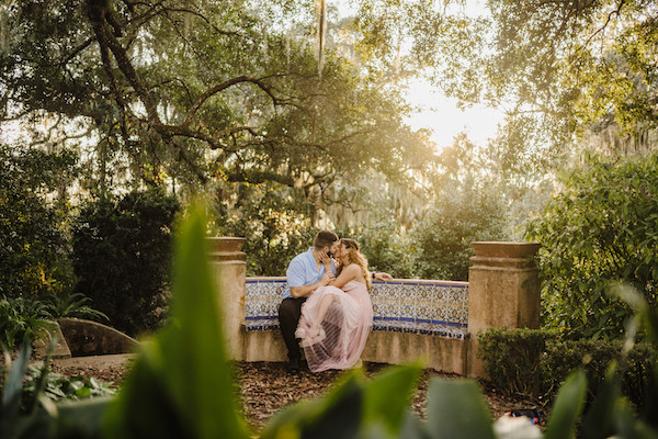 engaged couple kissing each other on bench during sunset