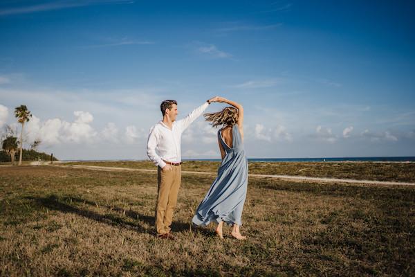 man twirling woman on grass