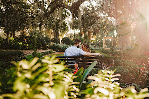 couple looking at each other sitting on a bench at bok tower gardens