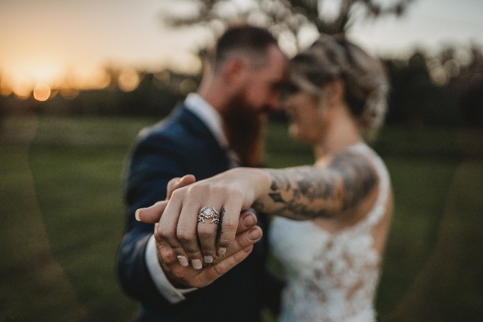 newly weds holding each other during sunset holding out wedding ring