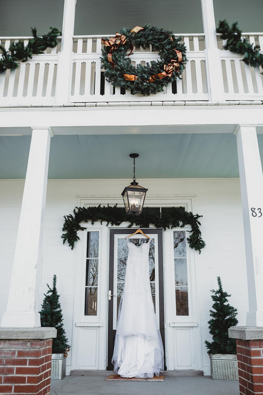 wedding dress hanging under beautiful christmas wreath on door