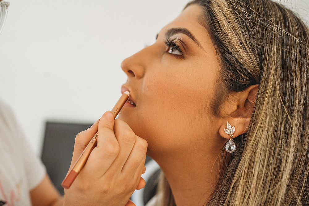 bride looking at make up artist while getting make up done