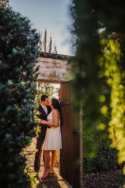 couple kissing between doorway during sunset