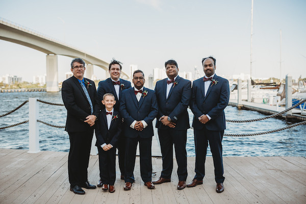 groomsmen together on pier with bridge behind them before ceremony