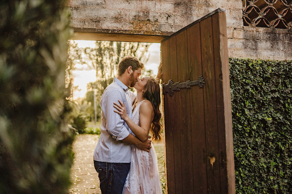 couple kissing in doorway for engagement photo