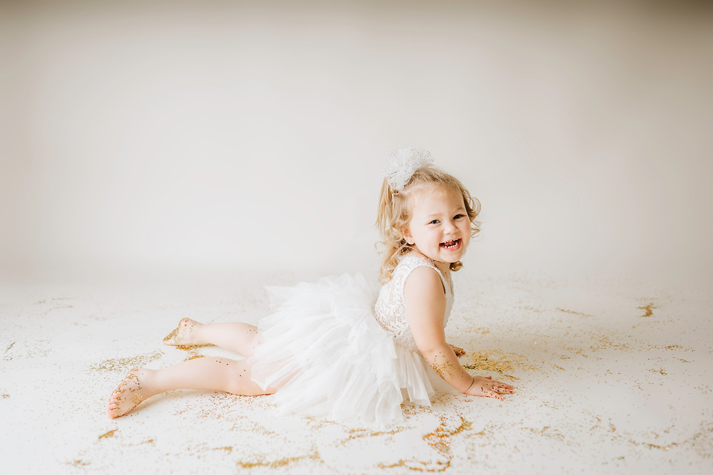 little girl smiling while laying on glitter