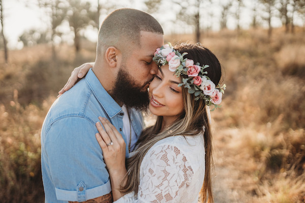 engaged couple holding each other in field at bok tower