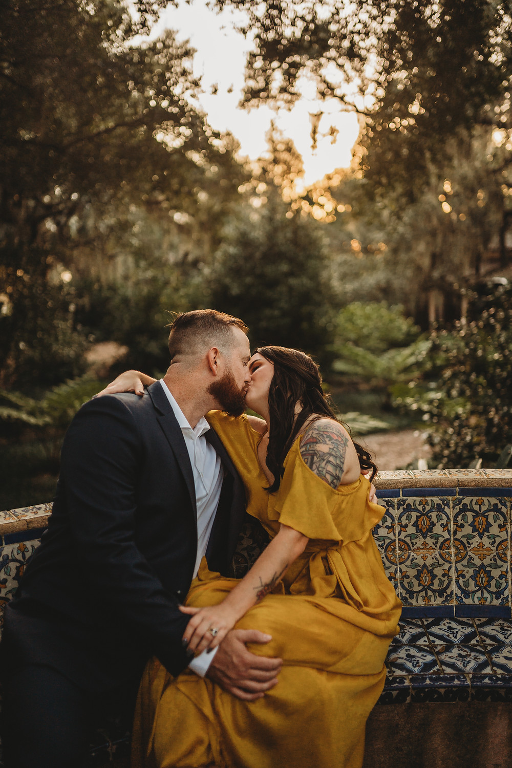 engaged couple kissing on a bench in bok tower gardens