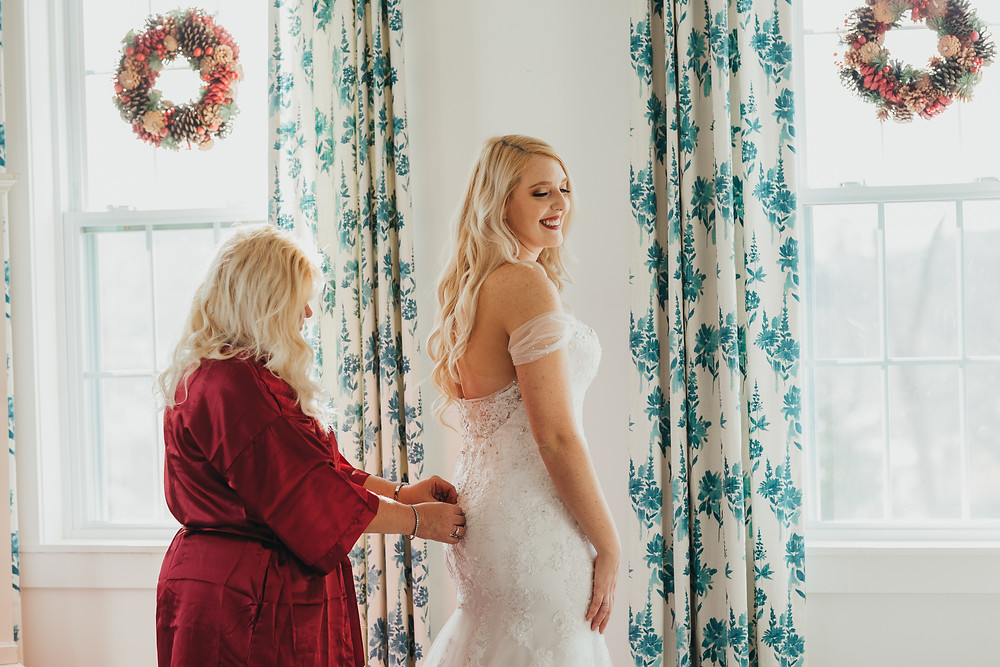 mom helping her daughter get dressed for ceremony