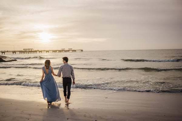 engaged couple holding hands on a beach during sunset