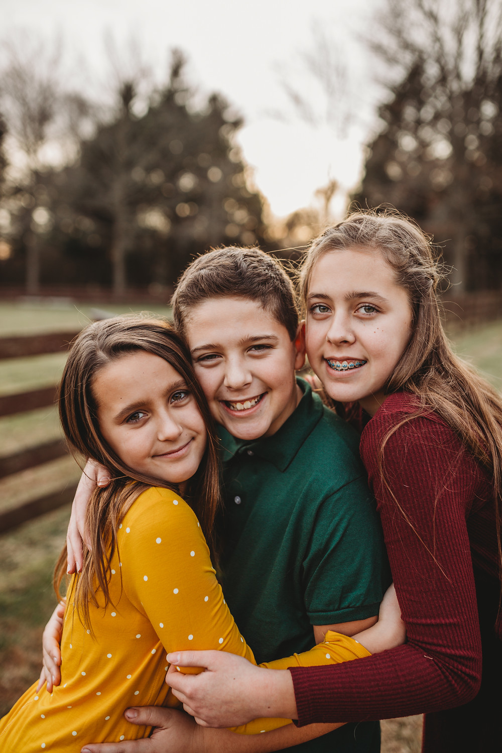 3 kids holding each other