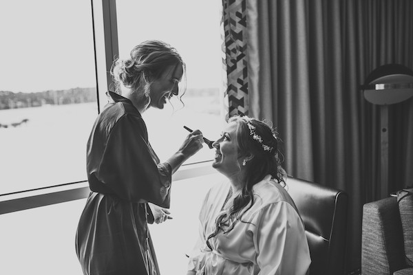 bride getting her makeup done before wedding ceremony