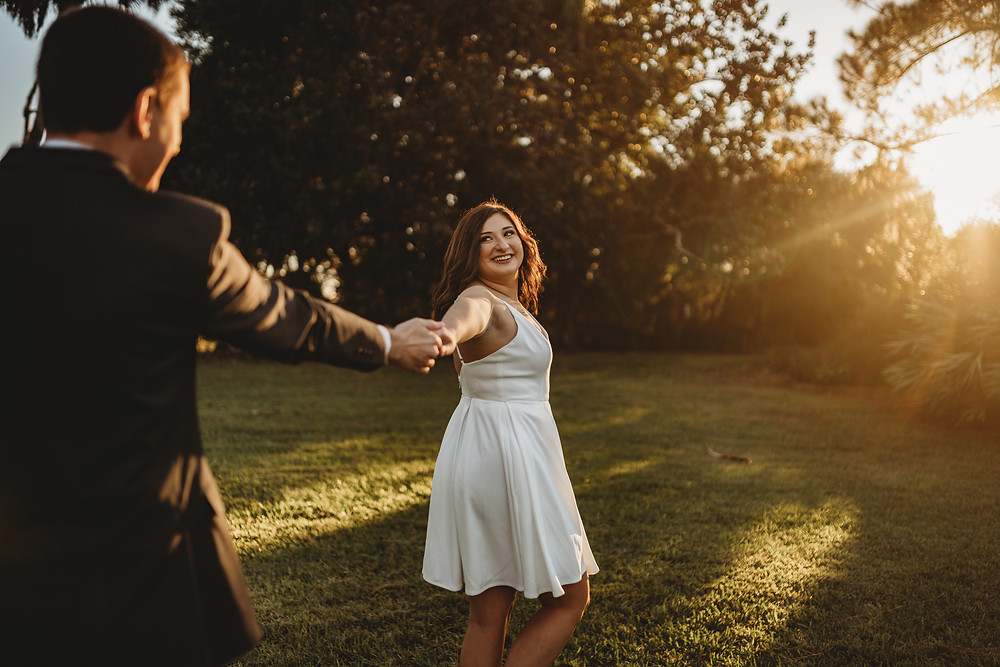 woman looking back at man holding his hand with sunset in background