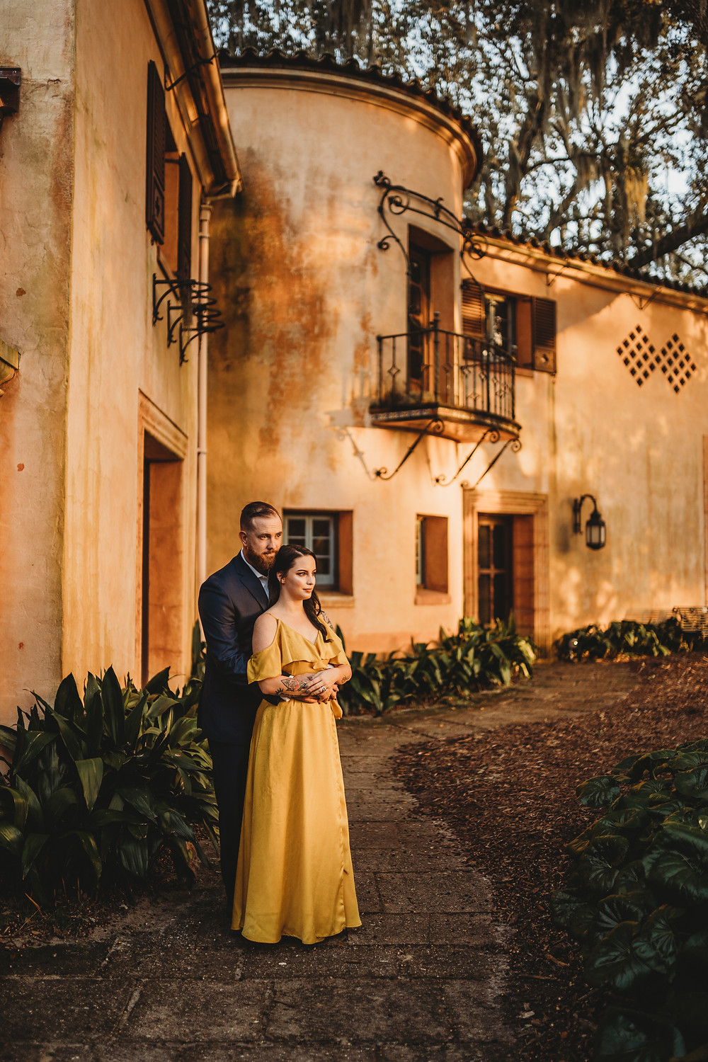 man standing behind woman in front of a rustic building watching the sunset