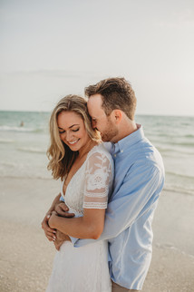 engaged couple getting photo taken on beach