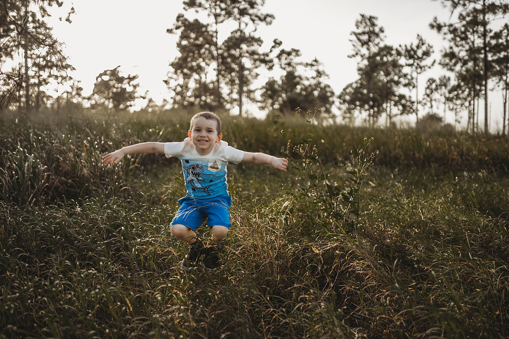 young boy being goofy jumping in the air in a field