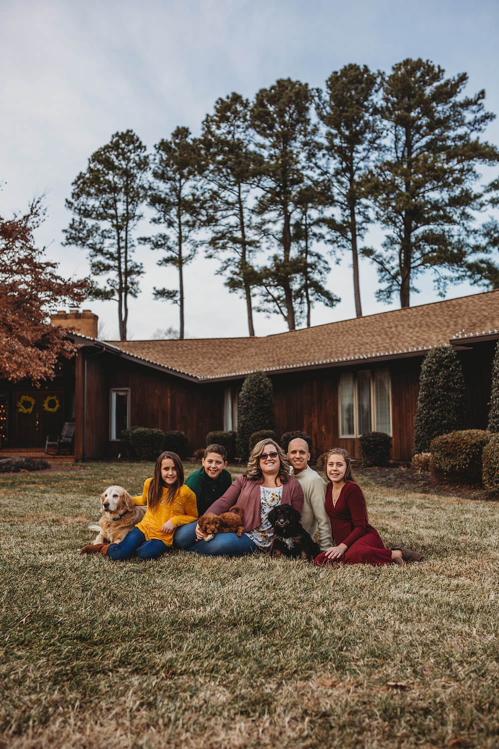 family sitting in grass in front of their home