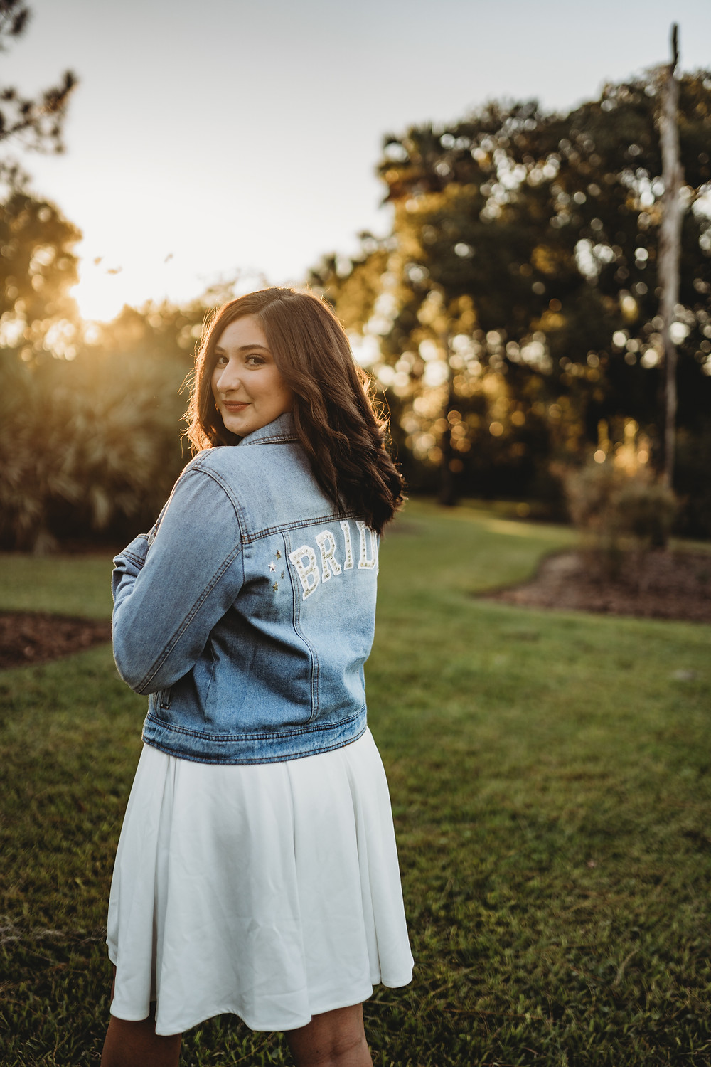 woman looking over shoulder during sunset with jacket on that says bride