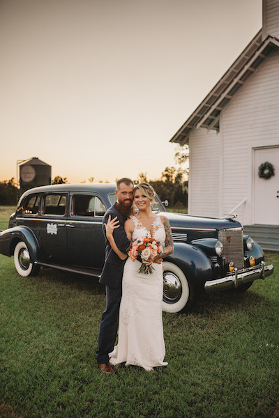 bride touching her husbands shoulder standing in front of an old car