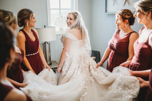 bridesmaids holding bridges wedding dress
