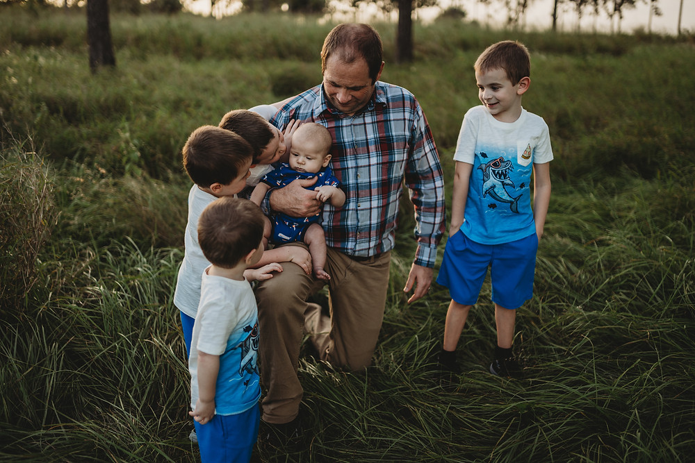 man with his five kids kneeling in a field at bok tower