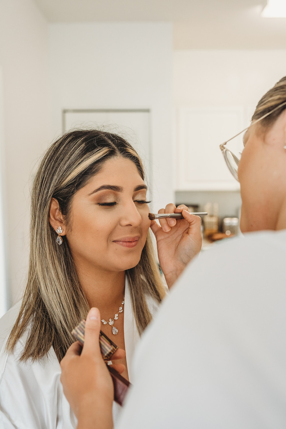 woman getting her make up done before getting married