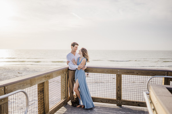 engaged couple looking at each other on a pier