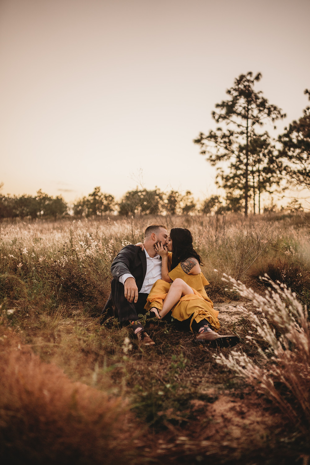 engaged couple kissing in a field at bok tower gardens