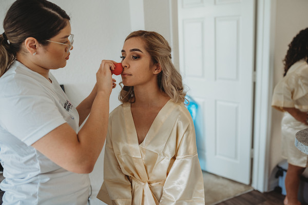 bride getting her make up done before ceremony