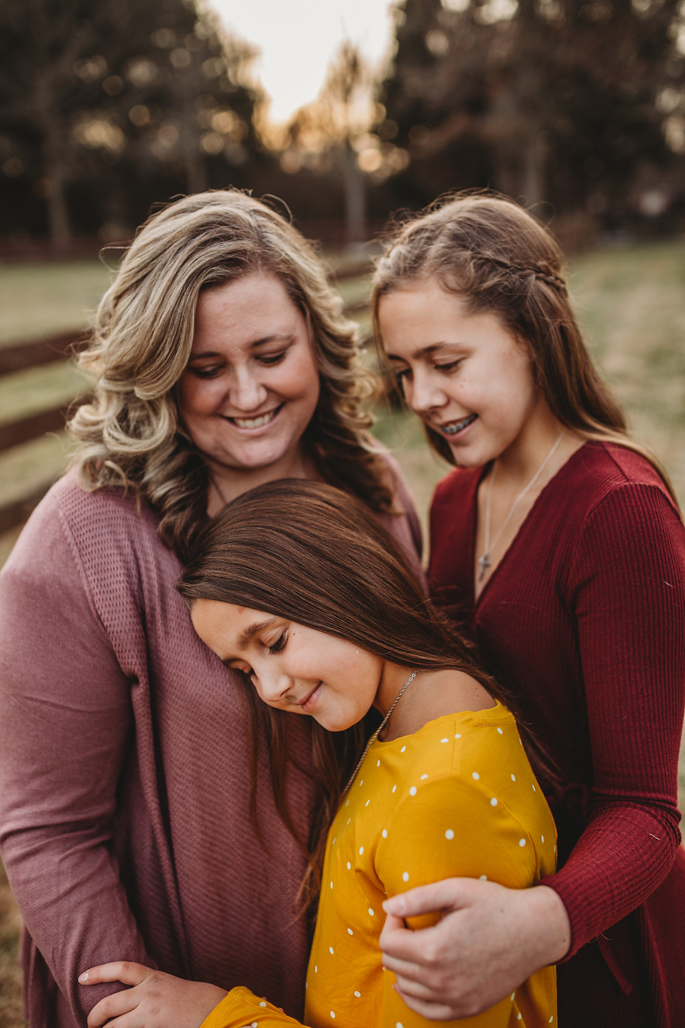 mom and her two daughters holding each other