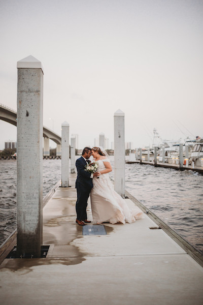just married couple touching foreheads on a pier at sunset
