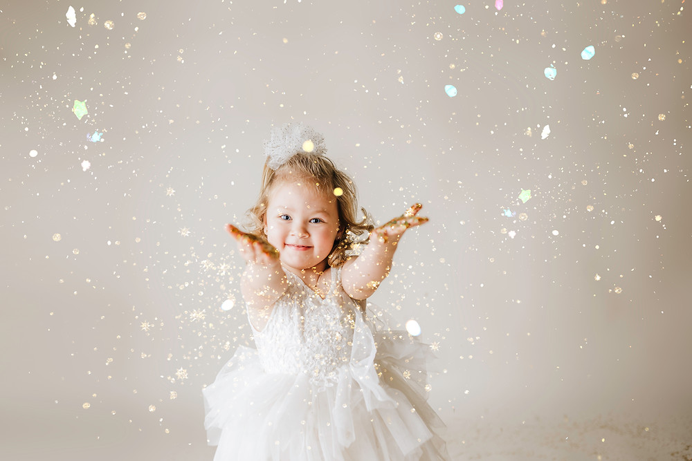 little girl throwing glitter and smiling