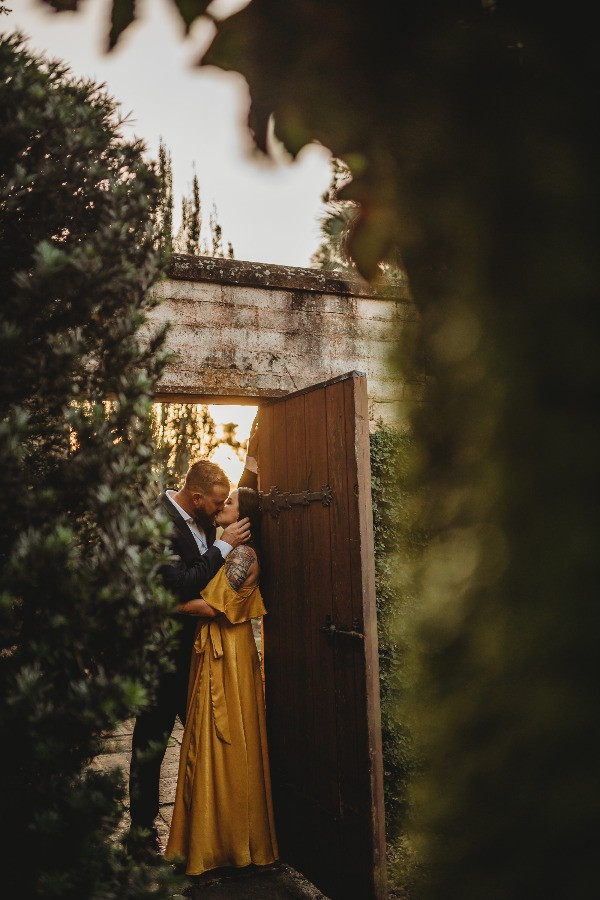 engaged couple kissing in doorway at bok tower