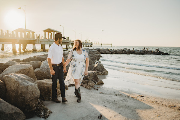 engaged couple holding hands during sunset on beach