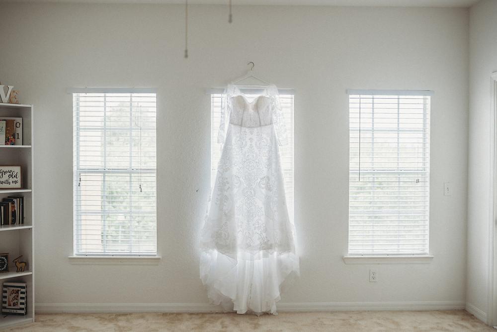 wedding dress hanging over a window