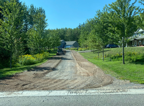 Reshaping a gravel road with a landscape rake