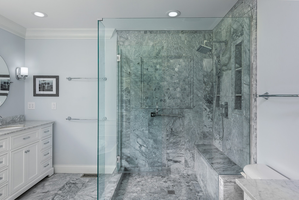 Marble tile walk-in shower with glass, custom niche, and bench seat | St Louis Renovators