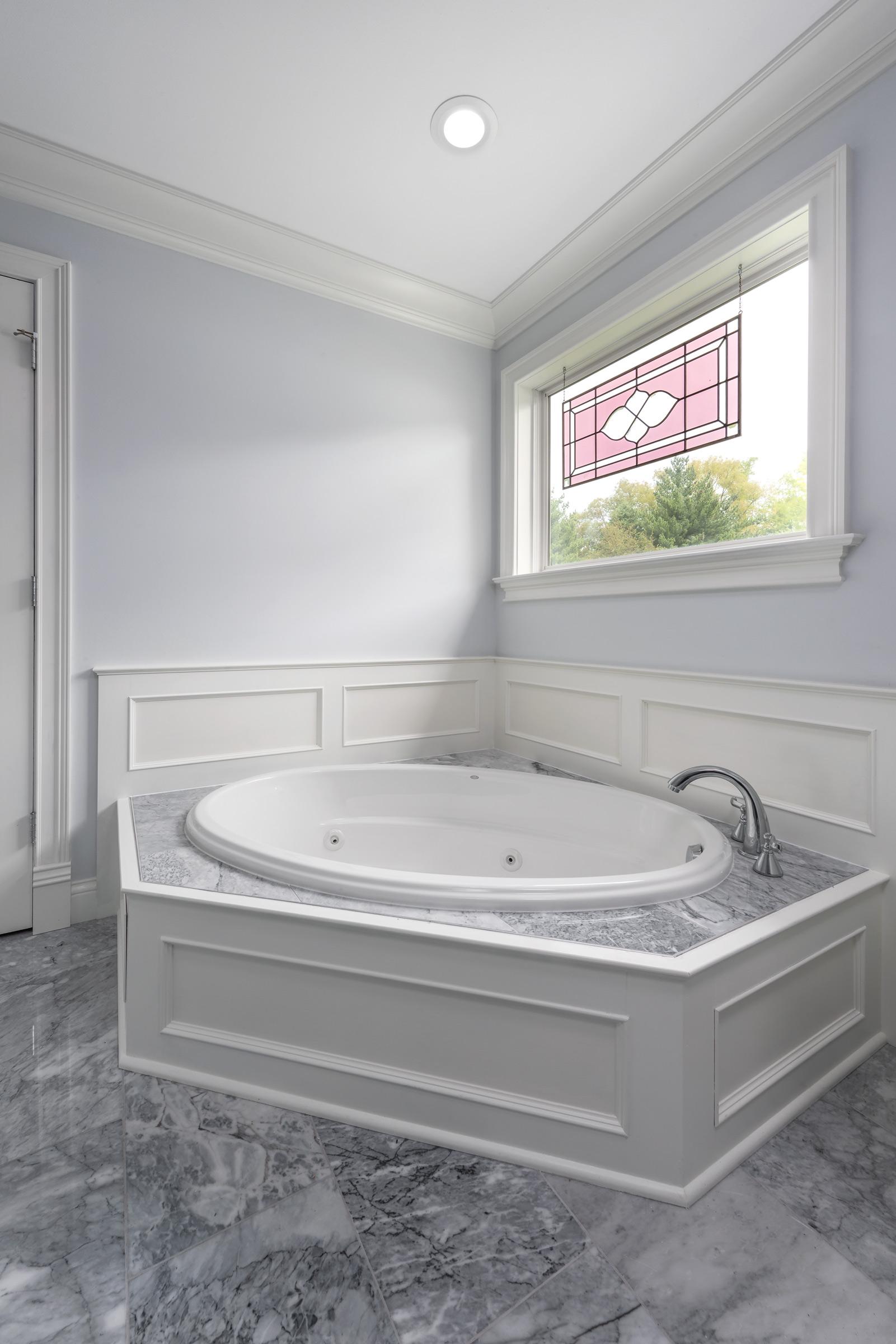Wood Paneling and marble tile bathtub ba