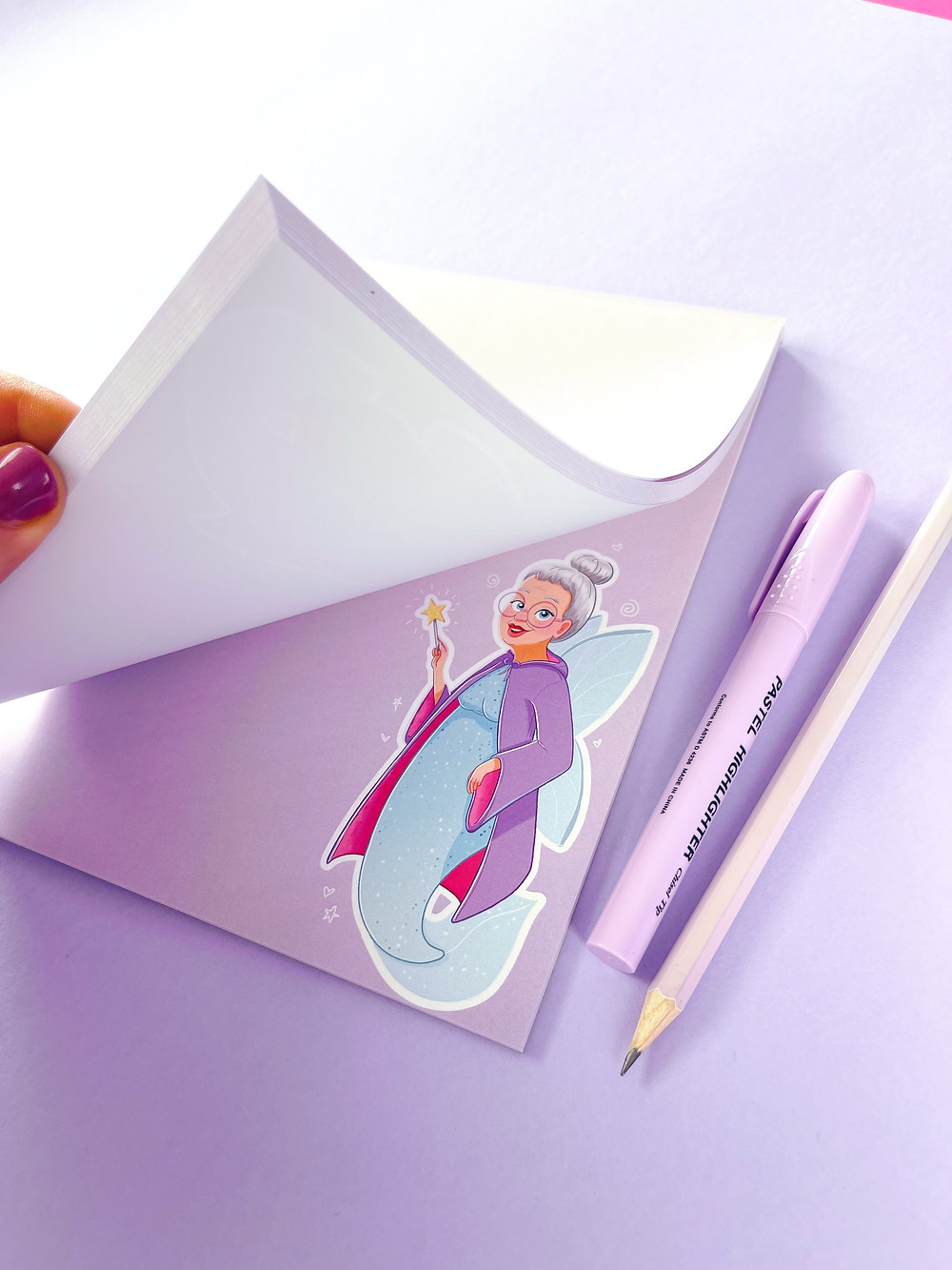 A notepad featuring a Fairy Godmother character by Emily Harvey Art