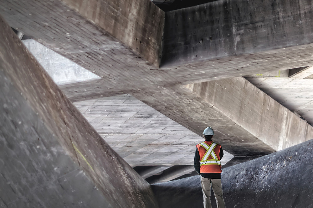 stock photo of construction worker surrounded by giant beams