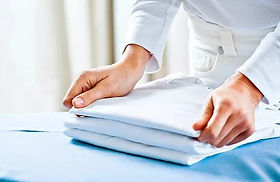 housekeeper folding ironed clothes