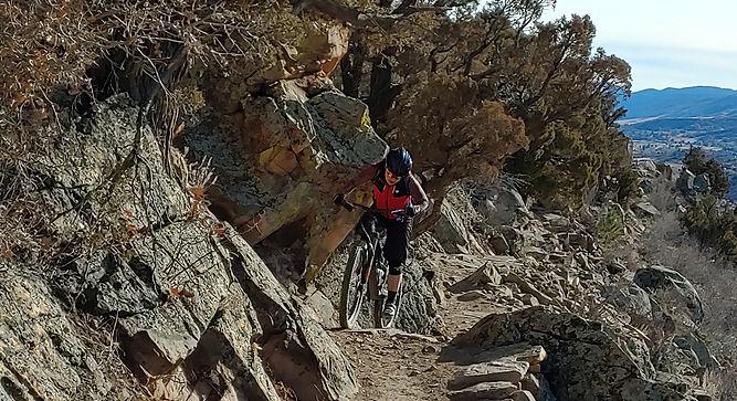 woman riding mountain bike hard