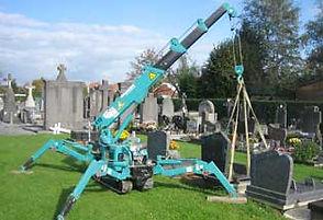 La mini grue est louée une journée pour poser une dalle dans un cimetière