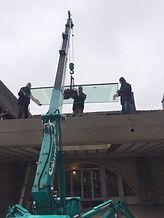 la mini grue pose une vitre sur un toit