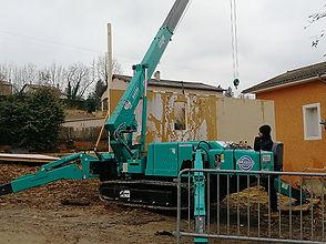 mini grue araignée construction immeuble sol terre