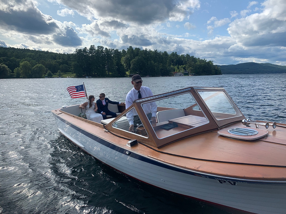 Bride and Groom arriving to wedding with Captain Ron and his wooden Lyman Love is On Lake George
