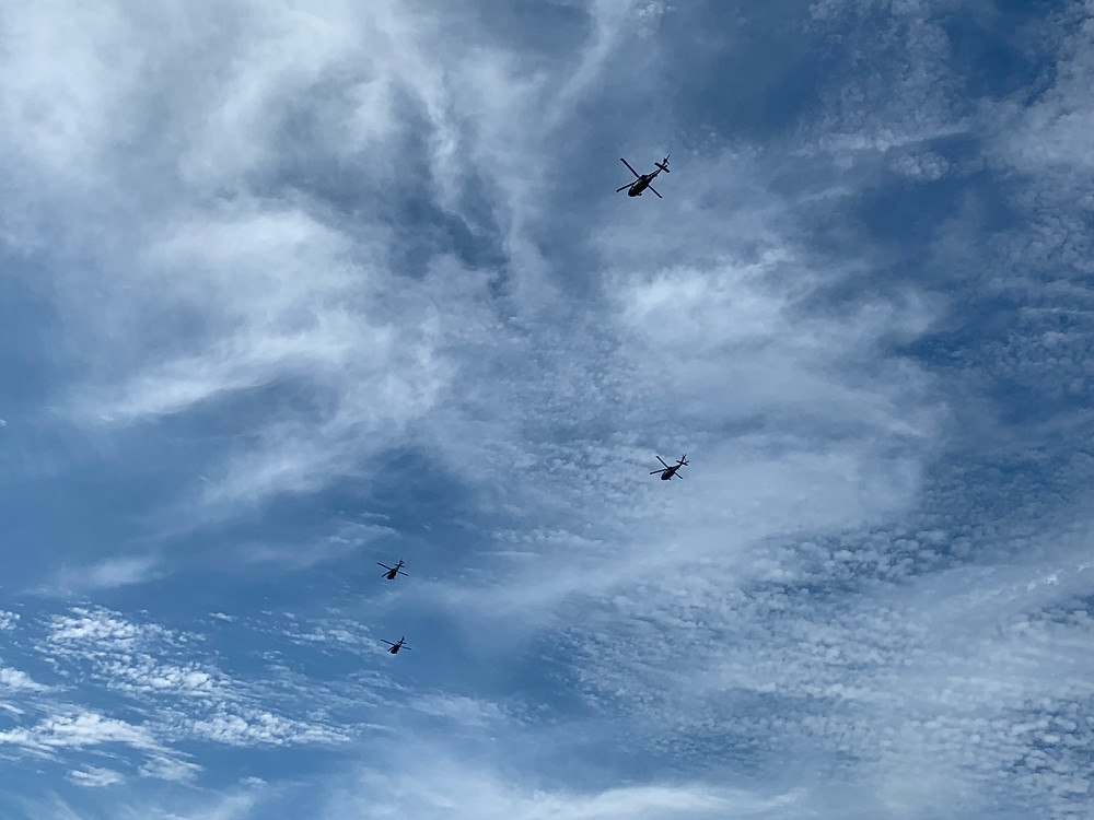 4 helicopters fly over Lake George in formation